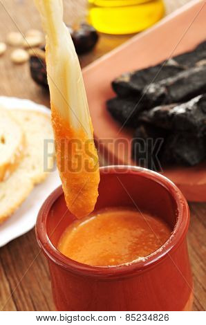 closeup of a barbecued calcot, sweet onion, dipped in romesco sauce, typical of Catalonia, Spain
