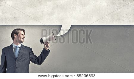 Young businessman with megaphone announcing some information
