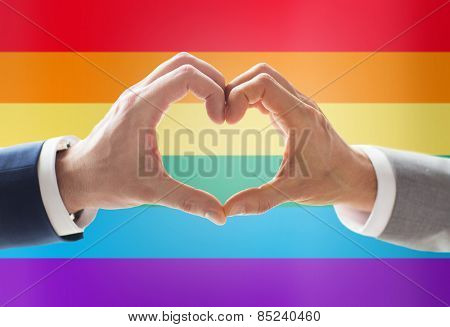 people, homosexuality, same-sex marriage, gesture and love concept - close up of happy male gay couple hands showing heart hand sign over rainbow flag background