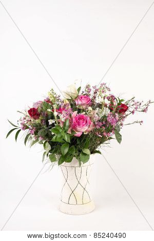 A beautiful flower arrangement in a vase set on a white islolated background. poster