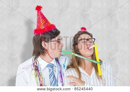 Geeky hipster wearing a party hat with blowing party horn against white background