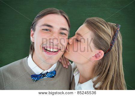 Pretty geeky hipster giving boyfriend kiss on the cheek against green chalkboard