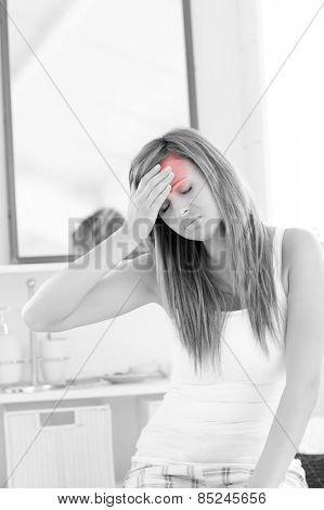 Dejected woman having a headache sitting in the bathroom at home
