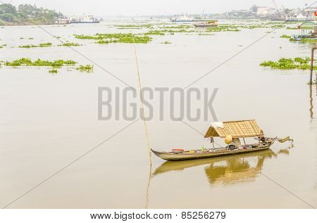 CHAU DOC, VIETNAM - JANUARY 2, 2013:  Local woman on her boat in port on Hau River (Bassac River)  in Chau Doc in Mekong Delta