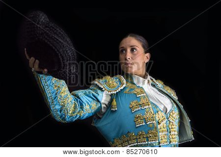 Woman Bullfighter Salutes With His Montera In Black Background