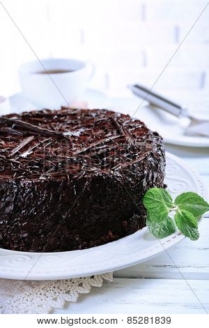 Tasty chocolate cake with cup of tea on table on brick wall background