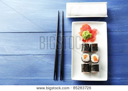 Sushi rolls with salmon on plate, on wooden background
