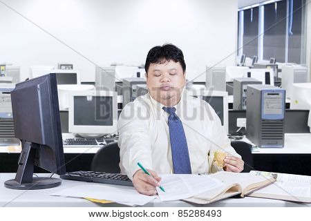 Asian Person Working While Eating In Office