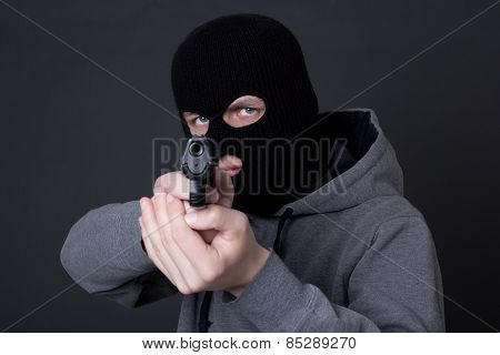 Masked Man Criminal Aiming With Gun Over Grey