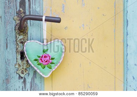 Handmade fabric heart hanging on an old door handle for a summer garden background.