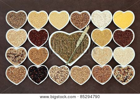 Grain and cereal food selection in heart shaped porcelain bowls over lokta paper background. Green freekeh wheat in large dish with ears.