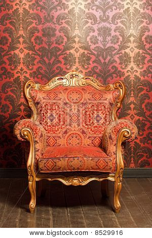 vintage red-yellow chair with gold accents standing beside the wall. wooden floor poster