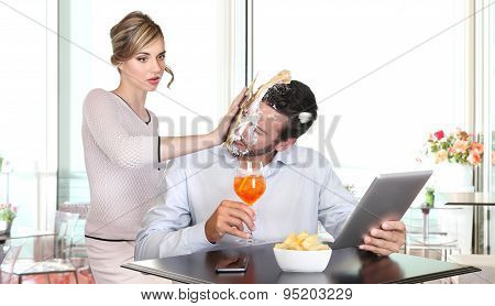 angry woman pulling cake in face to boyfriend cheating
