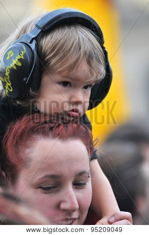 Child wearing ear muff for kids during a concert