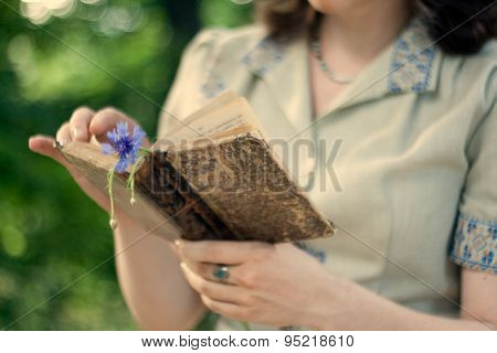 A Young Girl In A Vintage Dress Holding Old Book