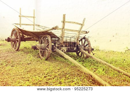 Vintage Old Rough Wooden Cart In Front Of Old Clay Wall.