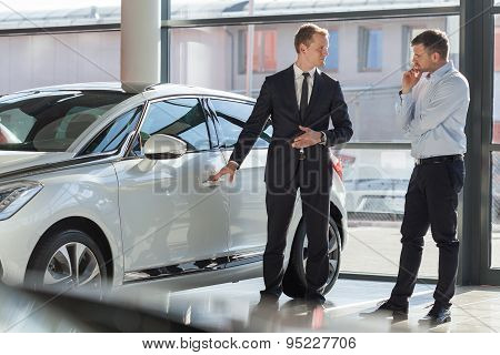 Car agent and customer in car showroom poster