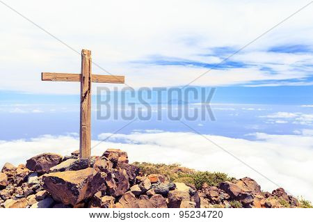 Christian wooden cross on mountain top rocky summit beautiful inspirational landscape with ocean island clouds and blue sky looking at scenic blue sea and white clouds. poster