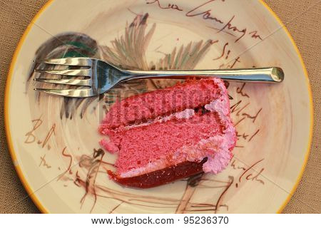 A slice of pink guava cake with pink frosting upclose on a plate with a chrome fork