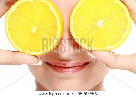 Woman Smiling While Holding Slices Of Lemon In Front Of Her Eyes