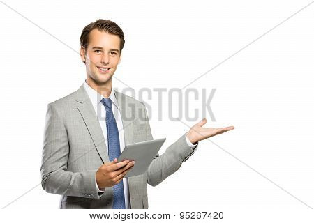 Young Businessman Holding A Tablet And Presenting Copyspace
