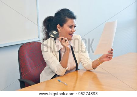 Business woman holds magnifier and is happy