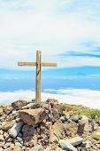 Christian cross on mountain top rocky summit beautiful inspirational landscape with ocean island clouds and blue sky looking at scenic blue sea and white clouds. poster