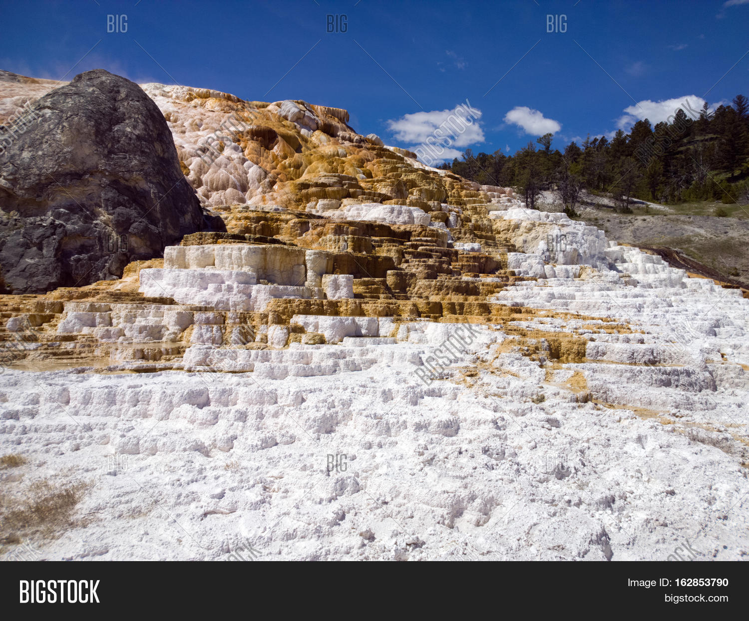 Red and white travertine terrace calcium carbonate deposits blue sky at Mammoth Hot Springs Yellowstone National Park