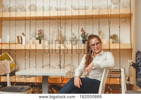 Young business woman sits at the table in own cafe.