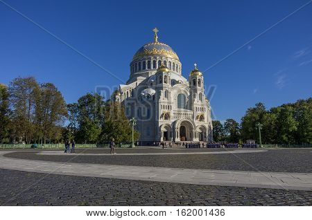 Naval Cathedral of St. Nicholas and the square with tourists and young naval cadets in Kronstadt at Sunny day