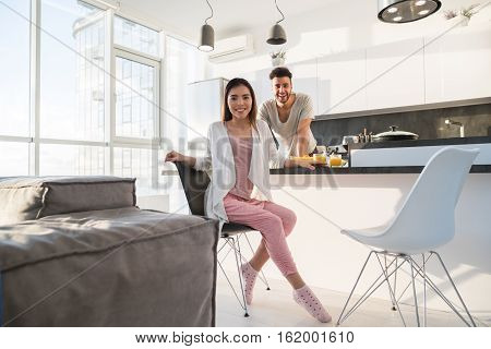 Young Couple Having Breakfast, Asian Woman Hispanic Man Cooking Food in Kitchen Modern Apartment Interior