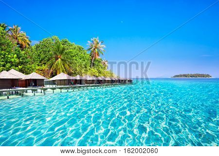 Overwater bungalows on tropical island with sandy beach palm trees and turquoise clear water
