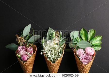 Composition of waffle cones with flowers and branches on dark background