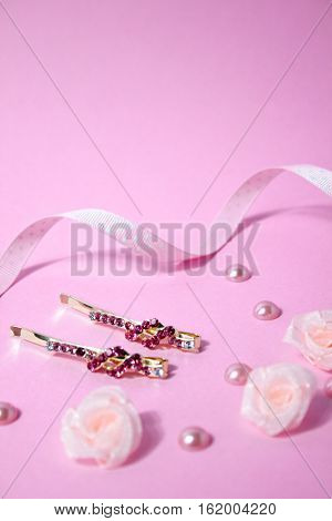 Golden hairpins with pink gemstone and pink ribbon on pink background