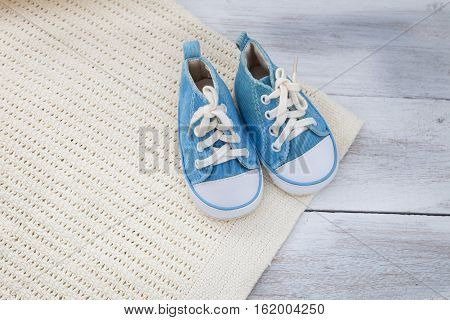 Shoes for a baby boy and a blanket on a white wooden background.top view