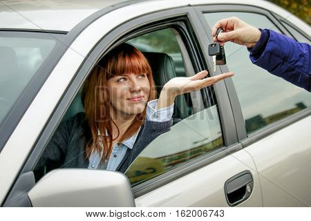 car keys handover. young woman sitting in car smiles as dealer hand over keys. concept of car sharing or leasing