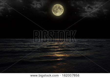 Beautiful magic blue night sky with clouds and full moon stars reflexion in water.