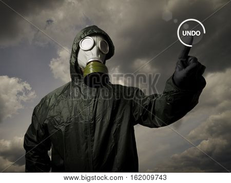 Man wearing a gas mask on his face. UNDO button concept.