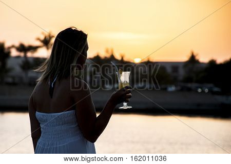 Amazing Sunset girl drink glass cocktail in Sultanate Oman at Souly Bay harbour and Hotels Oceanside