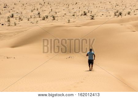 Man tourist in desert rub al khali in Oman running in sand