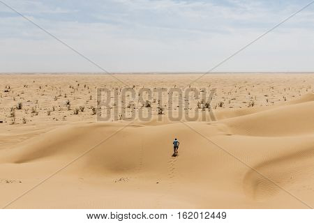 Man tourist in desert rub al khali in Oman running in sand 2