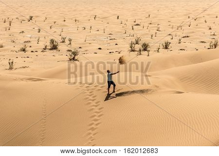Man tourist in desert rub al khali in Oman throwing sand 2