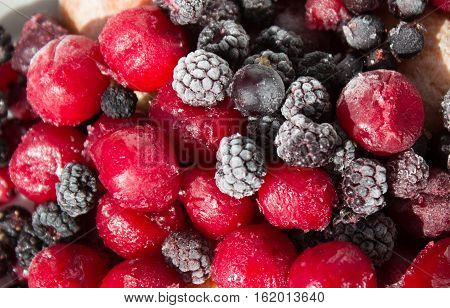 Close up of frozen mixed fruit berries - cherry raspberry blackberry black currant blurred background