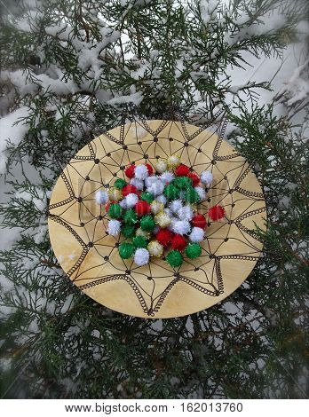 Red, white, green, and gold festive pom pom decorations form the center of a crocheted wire basket on a bamboo plate with evergreen branches in the background.  Vertical composition.
