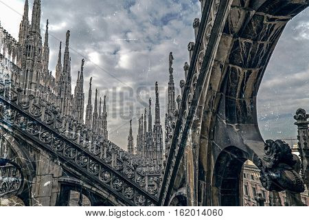 Old photo with architectonic details from roof of the famous Milan Cathedral Lombardy Italy. The famous spires. Vintage processing.