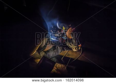 Welder worker with protective mask welding metal trunk pipeline in electrochemical protection work wear, night shift