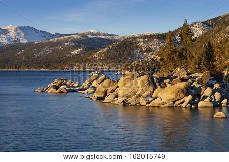 Sand Harbor Lake Tahoe Nevada at Sunset with rocks and trees on shoreline.