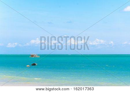 Joao Pessoa PB Brazil - December 8 2016: A tourist boat sails away on the beach of Joao Pessoa on a beautiful sunny day.
