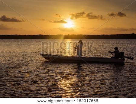 Joao Pessoa PB Brazil - December 8 2016: Man playing saxophone on a boat sailing in the waters of Praia do Jacaré beach. Man playing saxophone on golden hour a beautiful warm sunset.