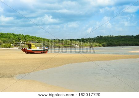 Boat jammed on a beach sandbar after tide go down. Sea water on the side and a background of green vegetation and a blue sky with many clouds.
